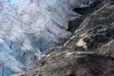 """A woman stands at the end of Exit Glacier's """"Edge of the Glacier"""" trail."""